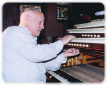 Sideview of Man Playing Pipe Organ